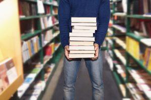 uomo in libreria che acquista libri tenendoli in mano tra corridoio e scaffali